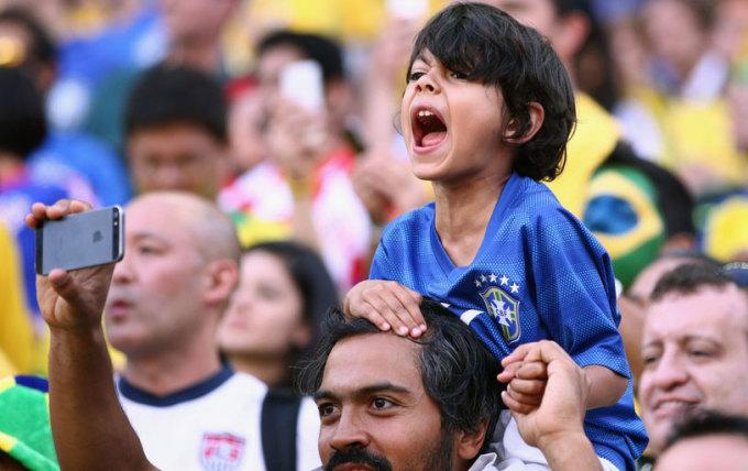 <p> Một ông bố dùng điện thoại chụp ảnh cậu con trai đang hét vang khi các tuyển thủ Brazil bước ra sân tập.</p>