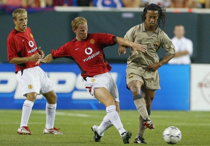 Nicky Butt (áo đỏ) tranh bóng vói Ronaldinho.