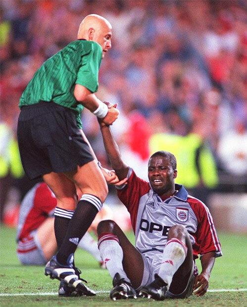 Collina an ủi Kouffour và kéo trung vệ của Bayern đứng dậy thi đấu nốt ít phút còn lại sau khi Man Utd nâng tỷ số lên 2-1 ở cuối trận chung kết Champions League 1999. Ảnh: UEFA.