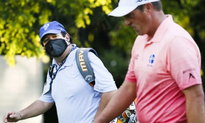 Caddie Todd Montoya đeo khẩu trang khi đi gần golfer Brian Stuard ở vòng đấu tập Charles Schwab Challenge trên sân Colonial hôm 10/6. Ảnh: USA Today.