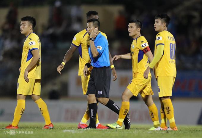 Cầu thủ SLNA quây trọng tài phản đối sau trận thua 1-2 trên sân Tam Kỳ ngày 5/7. Ảnh: Phi Hải