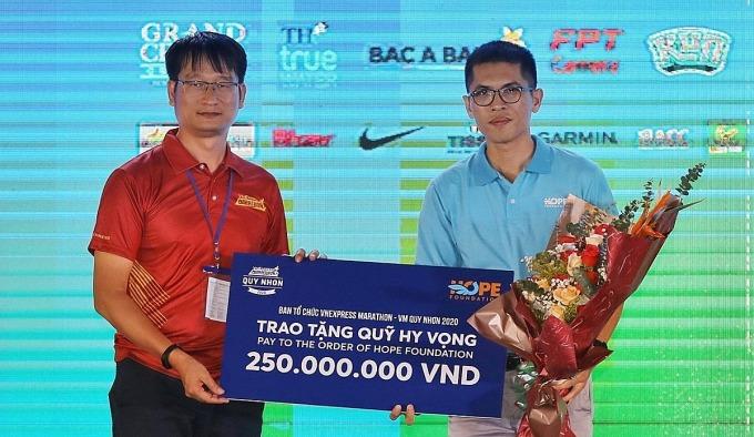 Ông Phạm Trọng Nghiệp (trái) - trưởng ban tổ chức VnExpress Marathon Quy Nhơn 2020 trao biểu trưng 250 triệu đồng cho đại diện Quỹ Hy vọng.