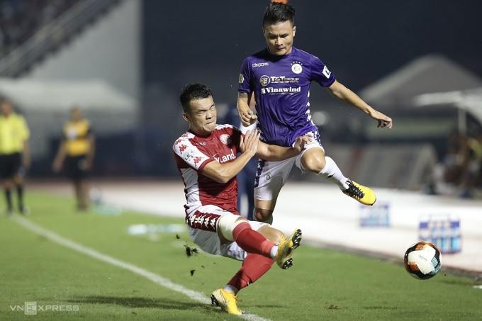 Quang Hải (áo tím) chịu sự truy cản của cầu thủ TP HCM, trên sân Thống Nhất chiều 24/7. Ảnh: Đức Đồng.