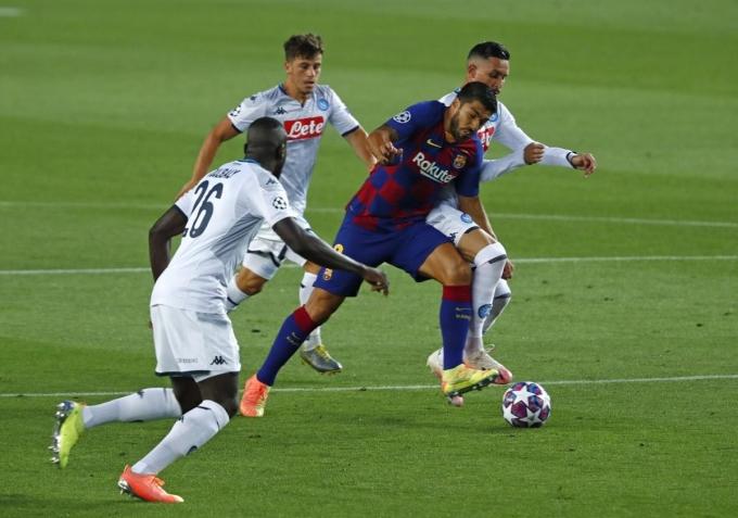 Suarez (xanh) trong vòng vây của các cầu thủ Napoli. Ảnh: AP.