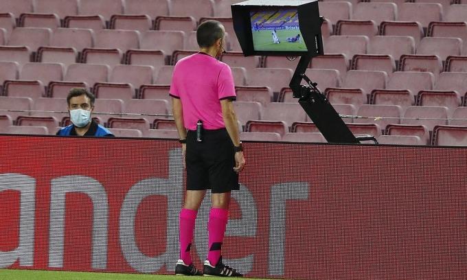 Trọng tài Cakir xem lại tình huống Messi bị phạm lỗi. Ảnh: AP.