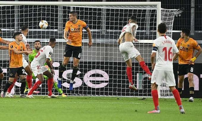 Hàng thủ Wolves (vàng) không thể đứng vững ở tình huống đánh đầu của Ocampos. Ảnh: Reuters.