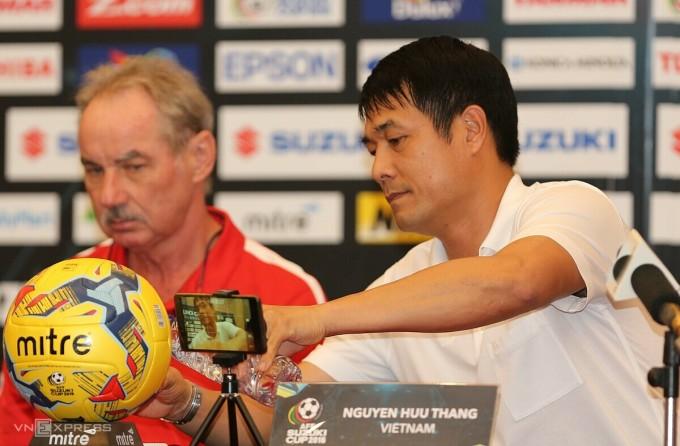 HLV Hữu Thắng rót nước mời thầy cũ Alfred Riedl trong cuộc họp báo ở AFF Cup 2016. Lúc này, ông dẫn dắt đội tuyển Indonesia. Ảnh: Đức Đồng.