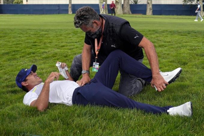 Koepka nhờ chuyên gia y tế chăm sóc trên green hố 12 vòng hai PGA Championship trên sân TPC Harding Park, San Francisco hôm 7/8. Ảnh: AP