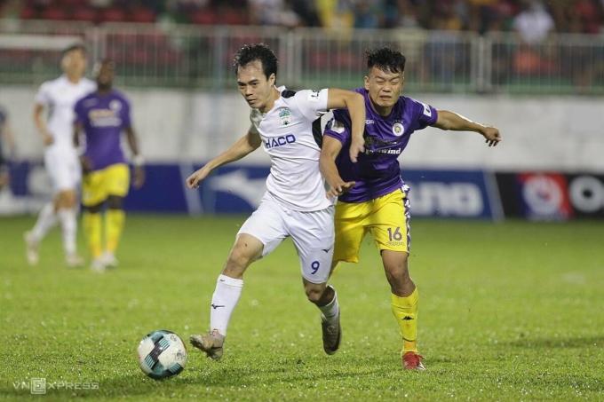 Văn Toàn (trắng) đi bóng trong sự truy cản của Thành Trung, khi HAGL thua Hà Nội 0-4 ở giải đoạn II hôm 15/10. Ảnh: Đức Đồng.