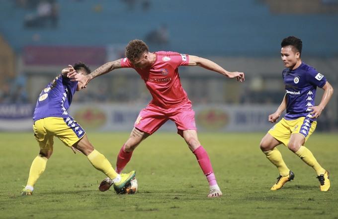 Geovane (hồng) tranh chấp bóng với cầu thủ Hà Nội. Ảnh: Lâm Thoả.