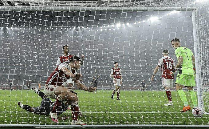 Hàng thủ Arsenal (đỏ) vào lưới nhặt bóng ở bàn thua thứ ba. Ảnh: AP.