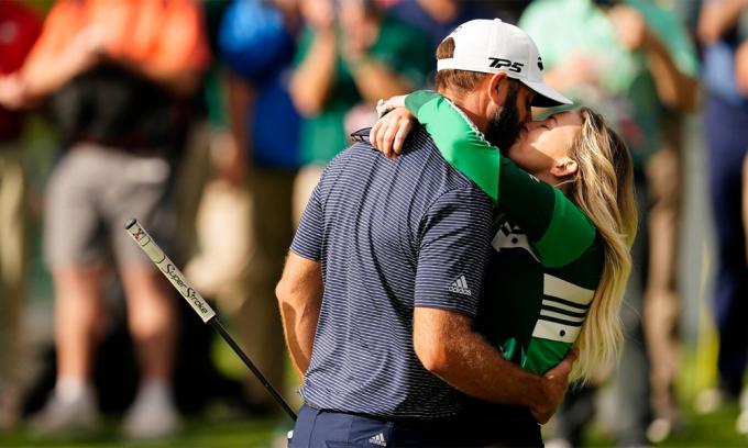 Johnson ôm chầm rồi đón nhận nụ hôn chúc mừng của bà xã Paulina Gretzky sau khi đủ điểm số để đăng quang hôm 15/11. Ảnh: Augusta National