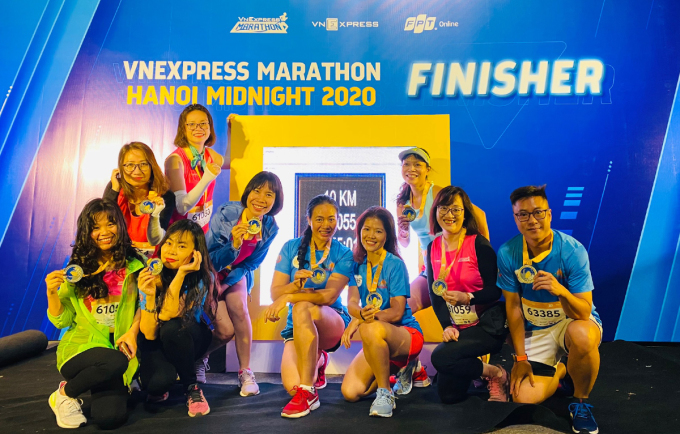Runner Hoàng Linh (thứ 5 từ trái sang) cùng những người bạn check-in tại bảng điện tử.