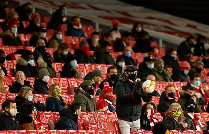 CĐV Arsenal đeo khẩu trang, ngồi cách nhau hơn 1 met, theo khuyến cáo của Chính phủ. Ảnh: AFP.