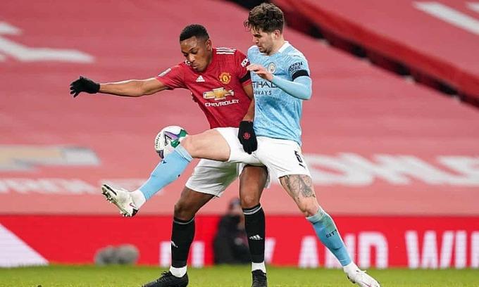 Martial (áo đỏ) tranh chấp bóng với cầu thủ Man City tối 6/1. Ảnh: AFP.