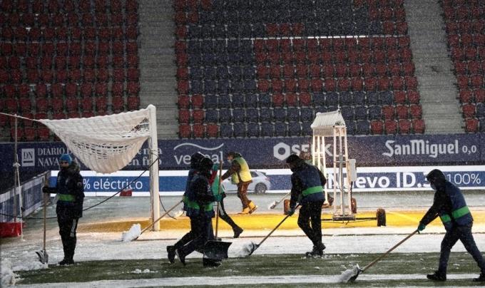 Nhân viên sân El Sadar dọn lớp tuyết phủ dày trên mặt sân không lâu trước giờ hai đội ra sân thi đấu. Ảnh: EFE