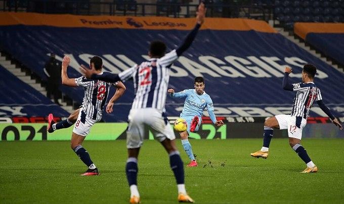 Cancelo (áo xanh) nâng tỷ số lên 2-0. Anh được Guardiola giao nhiệm vụ tối 26/1 và đều hoàn thành. Ảnh: PA.