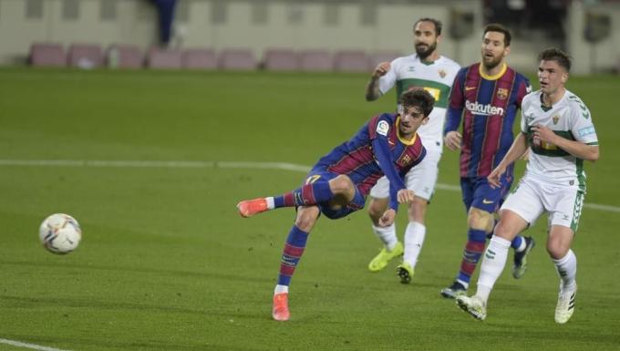 Messi chứng kiến pha dứt điểm hỏng ăn của đàn em Trincao trong hiệp một trận đá bù thắng Elche 3-0 hôm 24/2. Ảnh: EFE