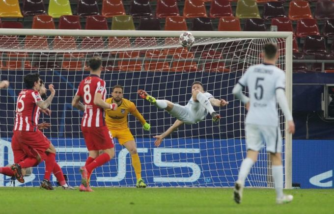 Giroud tung người ghi bàn trong thế quay lưng về phía cầu môn Atletico Madrid hôm 23/2. Ảnh: Reuters