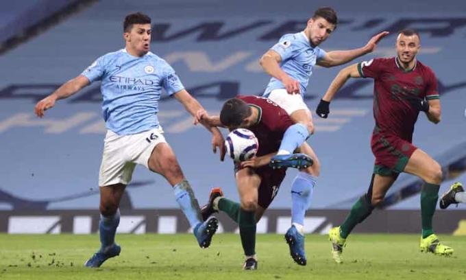 Coady đánh đầu gỡ hoà cho Wolves dù bị kẹp giữa hai cầu thủ Man City. Ảnh: Reuters.