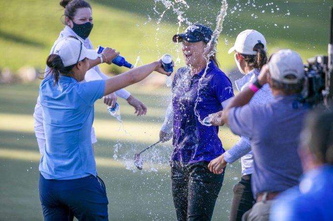 Danielle Kang (trái) đổ bia vào Ernst để chúc mừng sau khi golfer đồng hương vô địch Drive On. Ảnh: AP