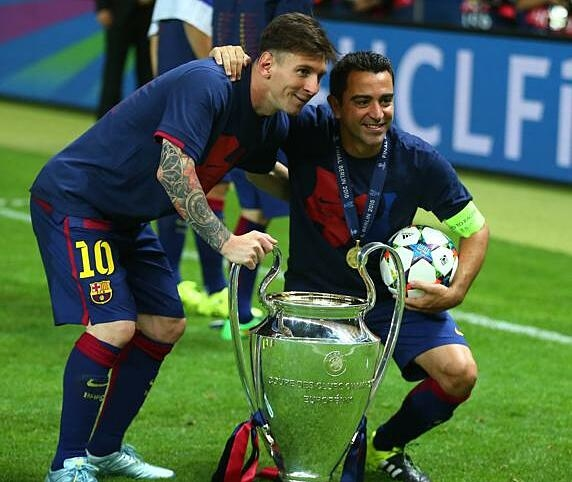 Messi (trái) và Xavi bên cạnh Champions League 2015 - lần gần nhất Barca vô địch đấu trường này. Ảnh: MD