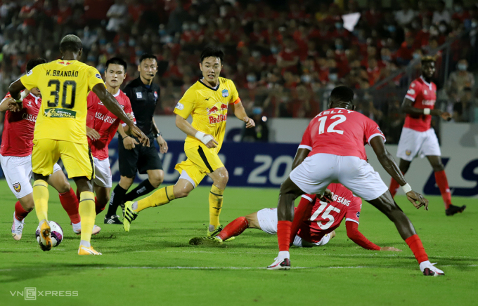 Hà Tĩnh (áo đỏ) chơi phòng ngự số đông để ngăn cản các cầu thủ tấn công của HAGL như Xuân Trường, Brandao. Ảnh: Đức Hùng
