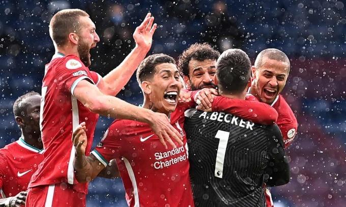 Các cầu thủ Liverpool ôm chầm lấy Alisson để chia vui sau khi thủ môn người Brazil ghi bàn quyết định ngay trước khi tan trận. Ảnh: Reuters