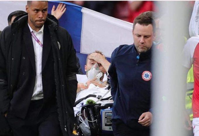 Ảnh chụp của phóng viên Reuters cho thấy Eriksen dường như đã tỉnh lại trên đường rời sân bằng cáng.