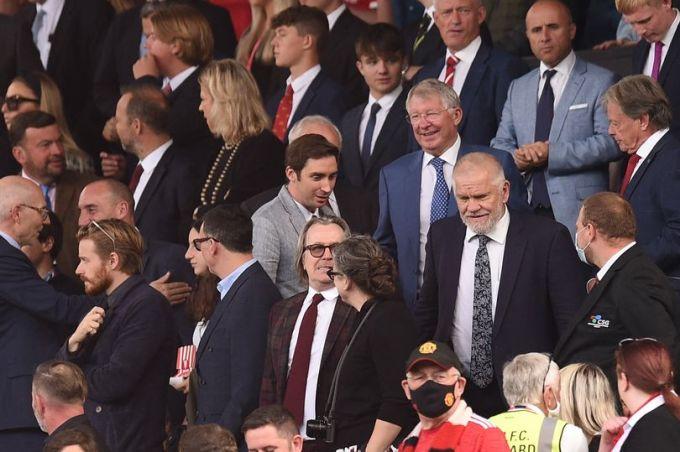 HLV Ferguson (đeo kính, vest xanh) tươi cười trên khán đài Old Trafford trước trận đấu Newcastle. Ảnh: AFP